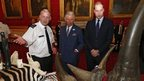 Princes Charles and William looking at items from endangered animals