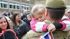 A girl hugs a soldier from the Duke of Lancaster&#039;s Regiment 