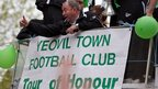 Manager Gary Johnson (C) waves as fans greet the Yeovil Town FC open-top tour bus as its does a celebration parade around the Somerset town on May 21, 2013 in Yeovil, England.