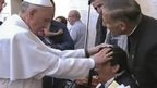 A screen grab of TV pictures showing the Pope laying his hands on a young man's head during Sunday Mass in an encounter which some claim was an attempted exorcism