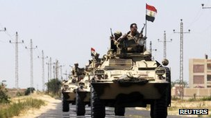 Soldiers in military vehicles proceed towards the al-Jura district in El-Arish