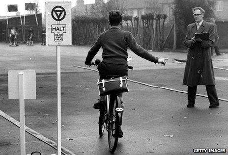 A pupil at a school in Harrow Weald, Middlesex, makes a right turn at a model halt sign during a cycling proficiency test in 1961
