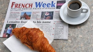 Coffee, croissant and English language paper