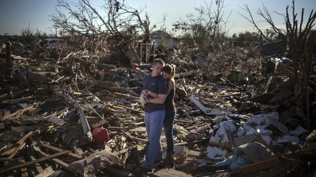 Danielle Stephan holds boyfriend Thomas Layton as they pause between salvaging through the remains of a family member's home after the Oklahoma tornado, 22 May 2013