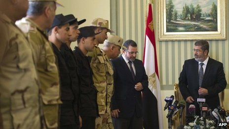 Egyptian President Mohammed Morsi (R) and Prime Minister Hisham Qandil (2R) welcome the policemen and soldiers (L) who were seized in Sinai by kidnappers at Almaza military Airbase in Cairo on Wednesday following their release