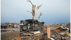 A pickup truck is wrapped around a tree  in Moore, Oklahoma