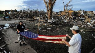 Survivors with a US flag among the ruins