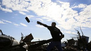 Jon Booth carries debris from his mother's tornado-destroyed home