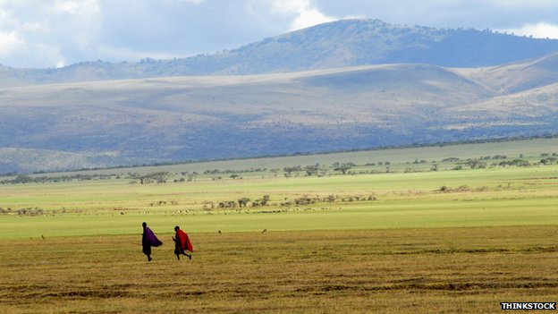 Two Maasai men walk in front of a mountain