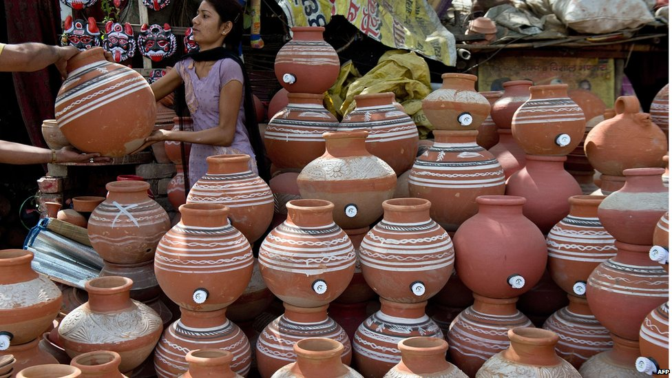 A customer checks earthen pots in New Delhi, 23 May