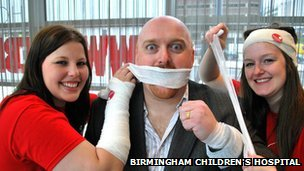 Nancy Gray and Rhianna Cooper from the fundraising team bandaging Pete Morgan