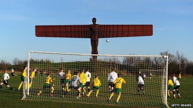 Boys play football in the shadow of the Angel of the North near Gateshead