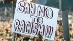 A fan holds a sign saying 'say no to racism' at a match