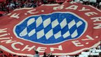 Bayern Munich supporters hold their club's logo aloft