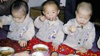 Young children eat a meal at a North Korea orphanage