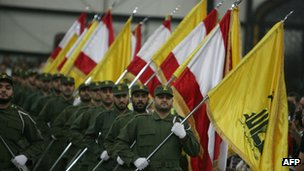 Hezbollah fighters, holding up national flags and the yellow flag of the militant Shiite Muslim group, parade on Martyrs Day in the southern suburbs of Beirut on 11 November 2009
