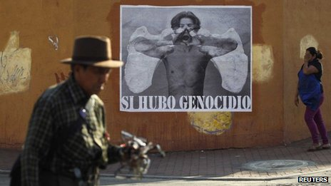 "Guatemalans pass a poster reading: ""Yes, there was a genocide"" in Guatemala City on 15 May 2013"