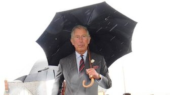 Prince Charles walks holding an umbrella