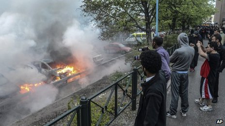 Bystanders watch burning cars in the Stockholm suburb of Rinkeby. 23 May 2013