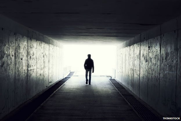 Man in tunnel walking towards light
