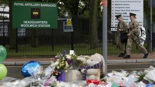 Soldiers pass flowers left in memory of murdered British solider Lee Rigby outside an army barracks in Woolwich