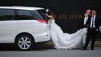 .A newly wed bride rests in the shade as her groom helps holding the hem of her wedding dress during their wedding photo session in Shanghai, China