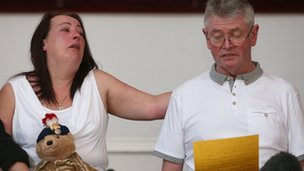 Lyn, comforts her husband and stepfather to Lee, Ian Rigby, as he reads a family statement,