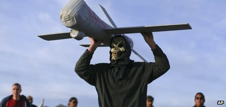 John Amidon holds up a model of an Air Force drone while protesting outside Creech Air Force Base, Wednesday, March 27, 2013, in Indian Springs