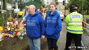 "Members of the public wearing ""Help for Heroes"" sweaters walk past flowers close to the scene where Drummer Lee Rigby of the 2nd Battalion the Royal Regiment of Fusiliers was killed"