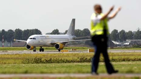 An airport worker in the taxi area at Amsterdam's Schiphol Airport, with a recently-landed plane visible in the background