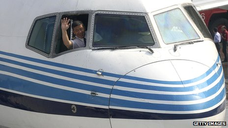 A pilot waves from the cockpit window at Songshan airport in Taipei, in 2008