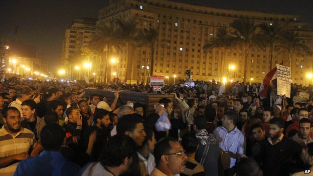Mourners carry a coffin from Cairo's Zeinhom mortuary to Tahrir square