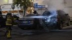 Swedish fireman puts out fire in a car in the Stockholm suburb of Tensta (25 May 2013)