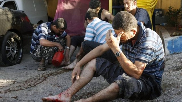Injured men are treated by friends after the rocket attack in Beirut, 26 May