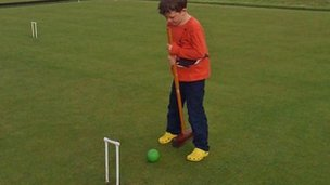 Child plays croquet