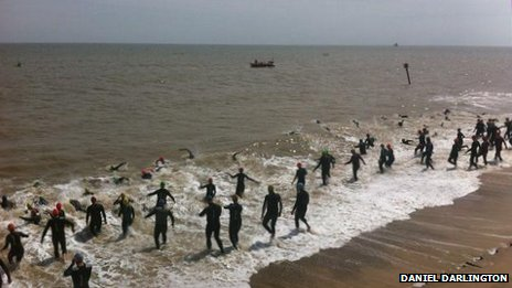 Swimmer enter the sea at Southwold