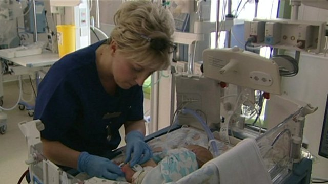 Nurse treating baby in neonatal unit
