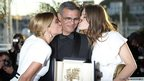 French actresses Lea Seydoux (L) and Adele Exarchopoulos kiss French-Tunisian director Abdellatif Kechiche on 26 May 2013