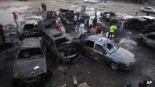 Iraqis gather at the scene of a car bomb attack at a used cars dealers parking lot in Habibiya neighbourhood of eastern Baghdad, Iraq, Monday, 27 May