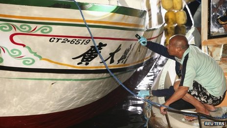 A fisherman stoops beside an investigator as they inspect the Guang Ta Hsin 28 fishing boat during an investigation of the vessel after its arrival in southern Taiwan on 11 May 2013
