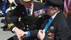 Royal Navy Commander Nick Chatwin shakes the hand of veteran George Hoggett, 89