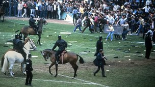 Mounted police drive back hooligans from the pitch at St Andrews during a second division match between Birmingham and Leeds in 1985