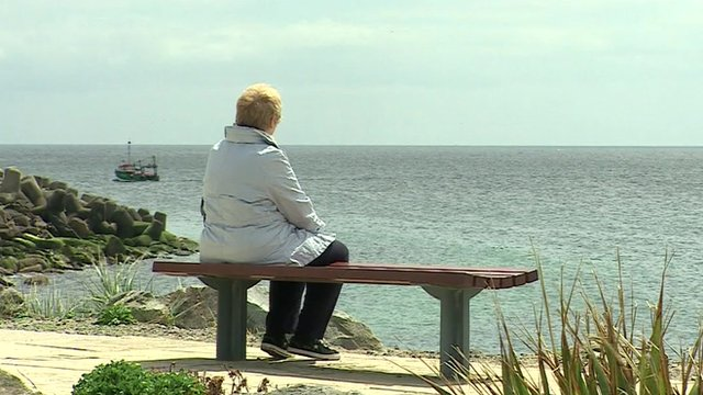 Woman on bench overlooking sea