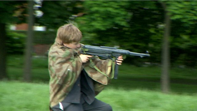 Child playing with a toy gun