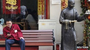 A man sits on a bench in front of a restaurant at a shopping district in Beijing