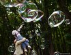 A girl plays with soap bubbles in a park in Kiev