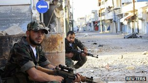 Free Syrian Army fighters patrol a street in Qusair town near Homs city