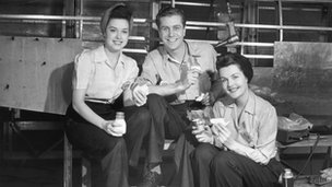 Two women and one man take a break while working in a factory.