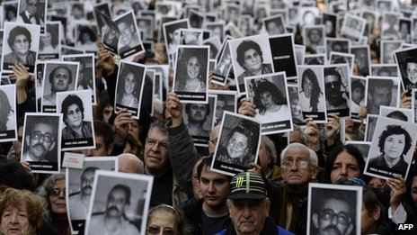 People hold portraits of victims of the terrorist bombing attack against the Argentine Israelite Mutual Association (AMIA) institute that killed 85 people and injured 300, blamed on Iran during the commemoration of its 18th anniversary, in Buenos Aires on 18 July 2012