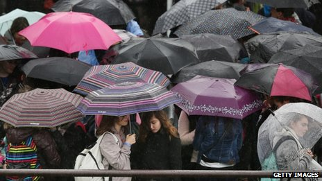 Passengers shelter under umbrellas as they wait on Westminster Pier on 28 May in London